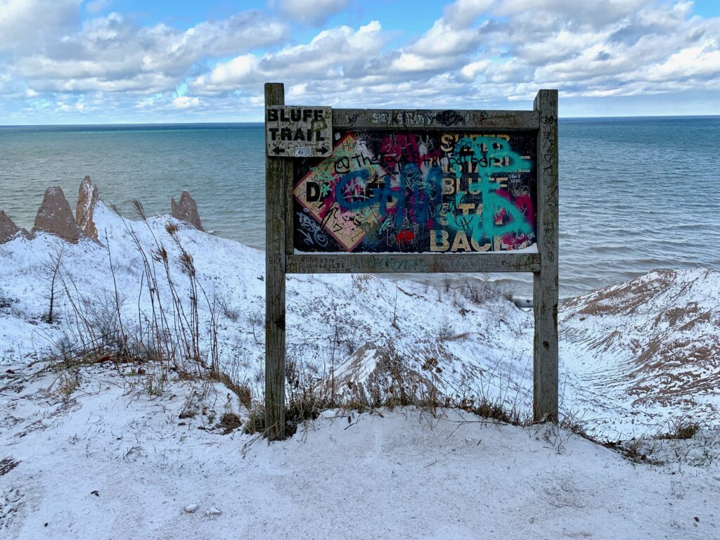 Caution sign covered in grafitti at Chimney Bluffs State Park